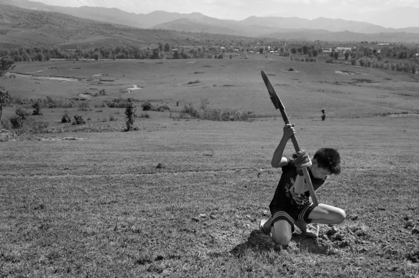 A boy digs for ant larvae to use in soup on a hillside overlooking the Plain of Jars. The area was intensively bombed and dozens of large craters can still be seen in the background.