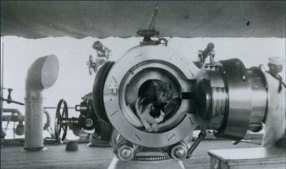"Ship's cats ""inspect"" the breech of a 4-inch gun aboard an unidentified US ship"