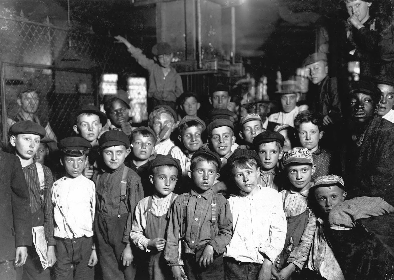 Lewis Hine - Indianapolis Newsboys waiting for the Base Ball edition, in a Newspaper office. Bad environment. Tough negroes etc., 1908